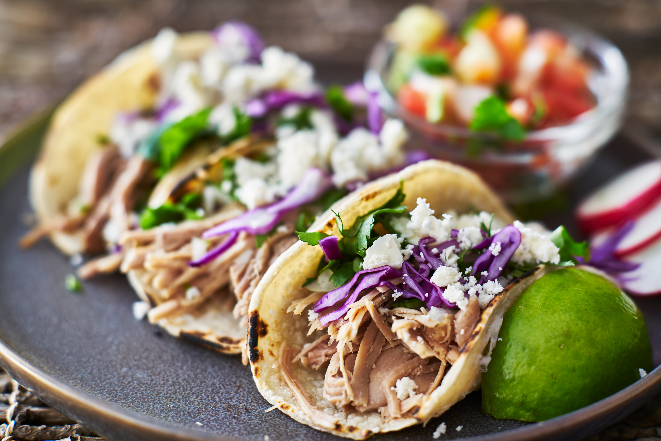 mexican street tacos with seasoned pork carnitas, red cabbage and queso fresco cheese